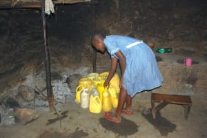 The Water Project: St. Martin's Primary School -  Pupil Adds To Kitchen Water Storage