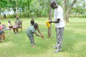 The Water Project: Imbinga Community, Imbinga Spring -  Handwashing With A Leaky Tin
