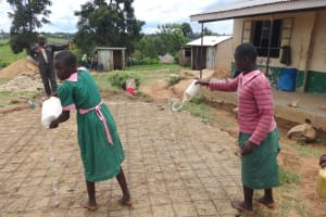The Water Project: Mwichina Primary School -  Pupils Pour Water Into Rain Tank Foundation