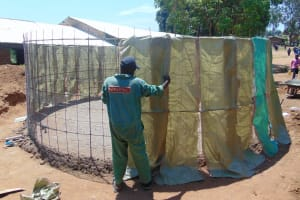 The Water Project: Mukama Primary School -  Tying Sugar Sacks To Wire Skeleton