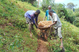 The Water Project: Jivovoli Community, Magumba Spring -  Community Members Bring Materials To Site