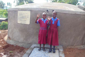The Water Project: Kipchorwa Primary School -  Girls Stand With Newly Completed Rain Tank