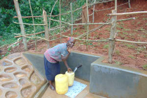 The Water Project: Jivovoli Community, Magumba Spring -  Woman Fetching Water