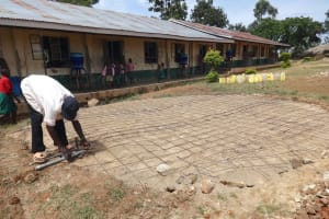 The Water Project: Mwichina Primary School -  Artisan Sets Access And Drainage Pipes In Tank Foundation