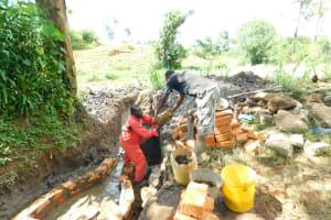 The Water Project: Imbinga Community, Imbinga Spring -  Passing Stones To Artisan