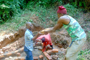 The Water Project: Kisasi Community, Edward Sabwa Spring -  Community Members Help Pass Bricks To The Artisan