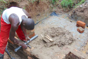 The Water Project: Kimarani Community, Kipsiro Spring -  Pipe Setting