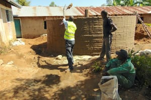 The Water Project: Mukama Primary School -  Shoveling Cement Into Tank For Use
