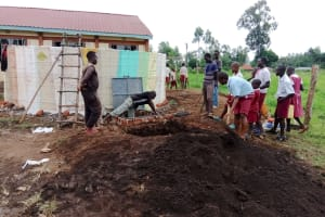 The Water Project: Mulwanda Mixed Primary School -  Shoveling Dirt Into Soak Pit