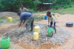 The Water Project: Kipchorwa Primary School -  Student Adds Water To Concrete
