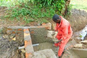 The Water Project: Imbinga Community, Imbinga Spring -  Cementing The Headwall