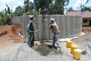 The Water Project: Ebukhuliti Primary School -  Shoveling Cement Into Tank For Use