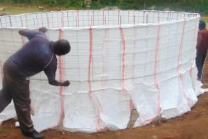 The Water Project: Kipchorwa Primary School -  Adding Sugar Sack Lining