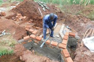The Water Project: Shikhombero Community, Atondola Spring -  Pipe Setting