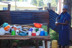 The Water Project: Gimomoi Primary School -  School Cook Washes Dishes Next To Dishrack
