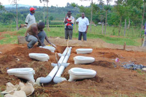 The Water Project: Kosiage Primary School -  Affixing Latrine Recepticles Into Pit Holes