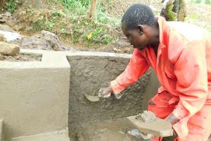 The Water Project: Imbinga Community, Imbinga Spring -  Plastering The Headwall