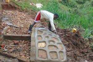 The Water Project: Jivovoli Community, Magumba Spring -  Rub Wall Construction