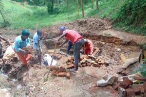 The Water Project: Bumira Community, Imbwaga Spring -  Passing Bricks To The Artisan