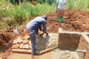The Water Project: Shikhombero Community, Atondola Spring -  Rub Wall Construction