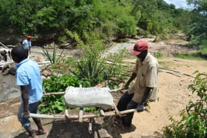 The Water Project: Kithumba Community E -  Carrying Cement Bag