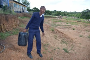 The Water Project: Kimuuni Secondary School -  Student Carrying Water
