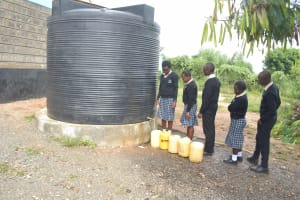 The Water Project: St. Paul Waita Secondary School -  Students At Small Plastic Water Storage Tank