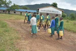 The Water Project: Ndithi Primary School -  Students Carrying Water