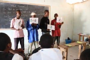 The Water Project: Lokomasama, Musiya, Nelson Mandela Secondary School -  Participants Hold Up Disease Transmission Posters