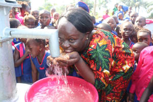 The Water Project: Lungi, Lungi Town, Holy Cross Primary School -  Teacher Drinks From The Well