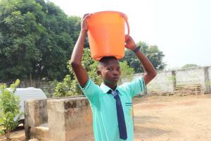 The Water Project: Lungi, Tardi, Khodeza Community School -  Student Carrying Water