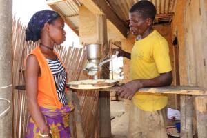 The Water Project: Kamasondo, Borope Village School -  Young Man Grinding Groundnut