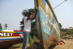 The Water Project: Lungi, Kamen, #22 Mission Road -  Young Man Repearing Boat