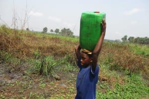 The Water Project: Lokomasama, Gbonkogbonko Village -  Small Boy Carrying Water