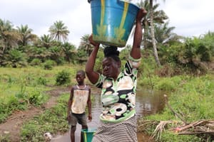 The Water Project: Kamasondo, Robombeh Village, Next to Mosque -  Young Lady Hoisting Up Bucket
