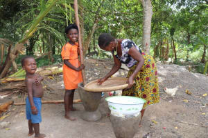The Water Project: Polloth Village, Kroo Town Area -  Woman And Daughter Processing Pounding Rice