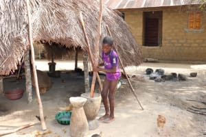 The Water Project: Polloth Village, Loco Area -  Child Pounding Rice