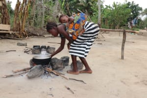 The Water Project: Kamasondo, Masinneh Village -  Young Lady Cooking Food