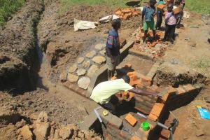 The Water Project: Tumaini Community, Ndombi Spring -  Kids Help Pass Bricks
