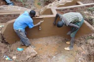 The Water Project: Kitulu Community, Kiduve Spring -  Plastering Inside Headwall