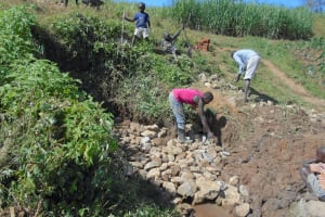 The Water Project: Kalenda A Community, Webo Simali Spring -  Community Helps Backfill With Stones