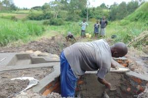 The Water Project: Emurumba Community, Makokha Spring -  Artisan Plastering As Kids Look On