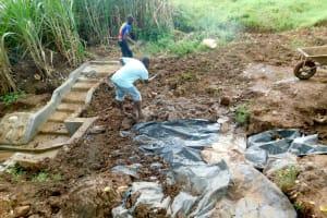 The Water Project: Namarambi Community, Iddi Spring -  Adding Tarp And Soil Over Stones