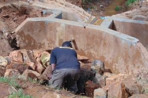 The Water Project: Kitulu Community, Kiduve Spring -  Backfilling With Stones