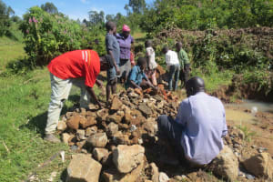 The Water Project: Tumaini Community, Ndombi Spring -  Community Delivers Stones