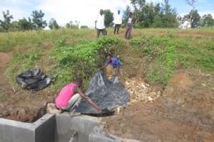 The Water Project: Kalenda A Community, Webo Simali Spring -  Laying Tarp Over Stones