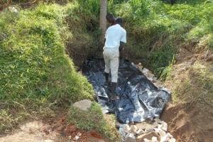 The Water Project: Kalenda B Community, Lumbasi Spring -  Adding The Tarp Over Backfill