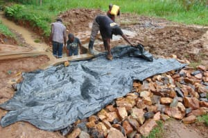 The Water Project: Kitulu Community, Kiduve Spring -  Adding Tarp To Backfilling