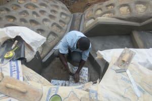 The Water Project: Tumaini Community, Ndombi Spring -  Tile Setting
