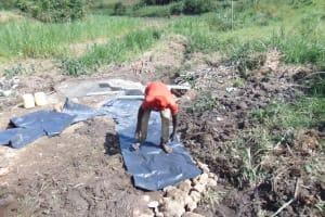 The Water Project: Emurumba Community, Makokha Spring -  Adding Tarp Over Backfilled Stones